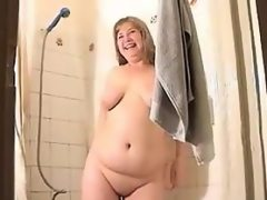 Fat blonde woman gets wet in the tub
